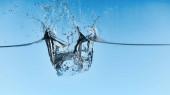 acqua limpida con cubetti di ghiaccio che cadono e spruzzi su sfondo blu