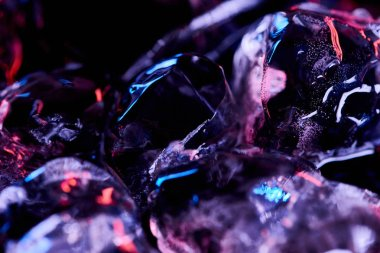 close up view of ice cubes with purple illumination isolated on black
