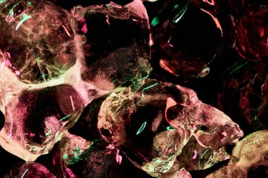 close up view of transparent ice cubes with red and green illumination isolated on black