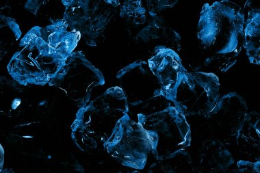 top view of frozen ice cubes with blue lighting isolated on black