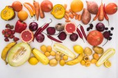 top view of assorted raw colorful autumn vegetables, berries and fruit on white background
