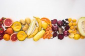 top view of assorted autumn vegetables, fruits and berries on white background