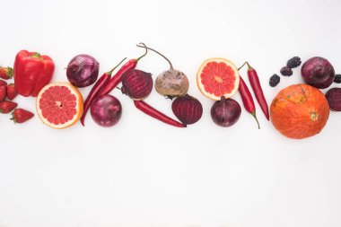 top view of raw red and purple autumn vegetables, berries and fruit on white background
