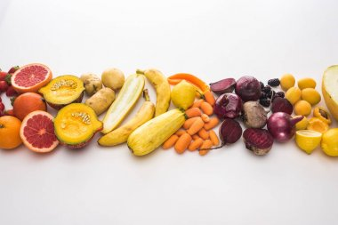 top view of red onions, beetroots, carrots, potatoes, apricots, melon, bananas, zucchini pumpkin and grapefruit on white background