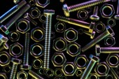 top view of scattered metallic bolts and nuts isolated on black