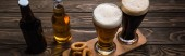 panoramic shot of glasses and bottles of dark and light beer near fried onion rings on wooden table