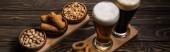 panoramatický záběr brýlí z tmavého a lehkého piva blízko mísy s oříšky, pistácie, smažený sýr a cibulové kroužky na dřevěném stole