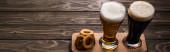 panoramatický záběr brýlí z tmavého a lehkého piva s pěnou u smažených cibulové kroužky na dřevěném stole