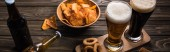 panoramic shot of glasses of light and bark beer near bottles and snacks on wooden table