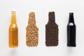 top view of bottles of dark and light beer near wheat and coffee grains isolated on white