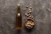 felülnézet tál pisztácia közelében üveg könnyű sör a barna felületre