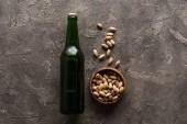 felülnézet tál pisztácia közelében zöld üveg sört a barna felületre