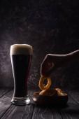 vágott kilátás az ember vesz sült hagymával gyűrű közelében pohár sört a fából készült asztal