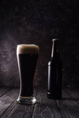 láhev u skleničky piva na dřevěném stole