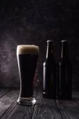 sklenice piva s pěnou u lahví na dřevěném stole