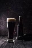 láhve a sklenice piva ve stínu na dřevěném stole