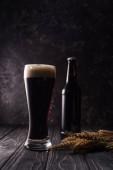 palack és pohár sör a búza tüskék közelében, fából készült asztal