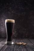 sklenice piva s pěnou v blízkosti pistácií na dřevěném stole