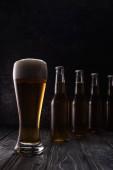 sklenice čerstvého lehkého piva s pěnou v blízkosti lahví na dřevěném stole