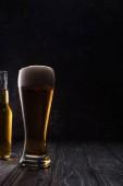 sklenice lehkého piva s pěnou v blízkosti láhve na dřevěném stole