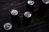 black metallic cans of beer on wooden table