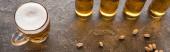 panoráma szemcsésedik-ból üveg könnyű sör mellett szétszóródott pisztácia-ra barna szövet felszín