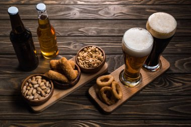 glasses and bottles of dark and light beer near bowls with peanuts, pistachios, fried cheese and onion rings on wooden table