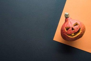 top view of spooky Halloween pumpkin on orange and black background
