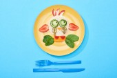 Photo top view of plate with fancy face made of food for childrens breakfast near cutlery on blue background