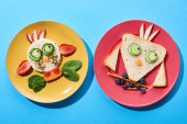 top view of plates with fancy cow and bird made of food for childrens breakfast on blue background