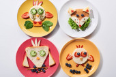 Photo top view of plates with fancy animals made of food for childrens breakfast on white background