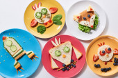 top view pf plates with fancy animals and rocket made of food for childrens breakfast on white background
