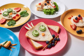 Photo plates with fancy animals made of food for childrens breakfast on white background