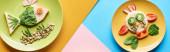 Fotografia vista dallalto delle piastre con animali fantasia fatti di cibo su sfondo blu, giallo e rosa