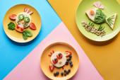 Top-Ansicht von Tellern mit ausgefallenen Tieren aus Lebensmitteln auf blauem, gelbem und rosa Hintergrund