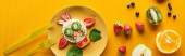 top view of plate with fancy cow made of food on colorful orange background, panoramic shot