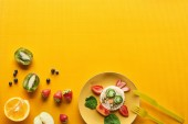 Fotografia vista superiore del piatto con mucca fantasia fatta di cibo su sfondo arancione colorato