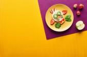 Fotografia vista superiore del piatto con mucca fantasia fatta di cibo su sfondo viola e arancione