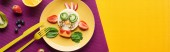 top view of plate with fancy cow made of food with cutlery on purple and orange background, panoramic shot