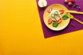 Photo top view of plate with fancy cow made of food with cutlery on purple and orange background
