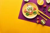 pohled na talíř s ozdobnou krávou z potravin s příbory na purpurovém a oranžovém pozadí
