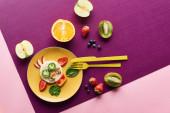 Fotografia vista superiore del piatto con mucca fantasia fatta di cibo vicino frutti su sfondo viola