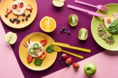 top view of plates with fancy animals made of food near fruits on purple background
