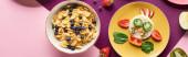 Fotografie pohled na talíře s ozdobnou krávou z potravin v blízkosti ovoce a snídaně vločky na purpurovém pozadí