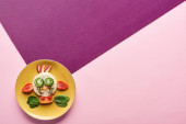 top view of plate with fancy cow made of food on pink and purple background