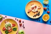 Top-Ansicht von Tellern mit ausgefallenen Tieren aus Lebensmitteln auf blauem und rosa Hintergrund