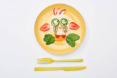 top view of plate with fancy cow made of food for childrens breakfast near cutlery on white background