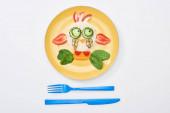 pohled na talíř s ozdobnou krávou z jídla pro děti, které jsou blízko příborů na bílém pozadí