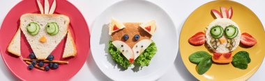 Top view of plates with fancy cow, bird and fox made of food for childrens breakfast on white background, panoramic shot stock vector