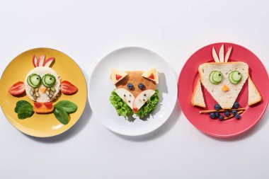 Top view of plates with fancy cow, bird and fox made of food for childrens breakfast on white background stock vector